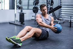 Muscular man doing russian twist exercises Stock Photos