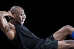 Muscular man doing sit ups with eyes closed. Against black background stock images