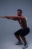 Muscular man doing squats Stock Photography