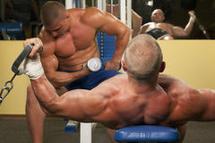 Muscular man doing weightlifting in gym Stock Photos