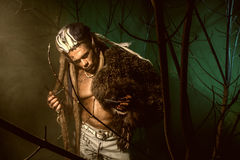Muscular man with dreadlocks and skin through the trees and mist Stock Image