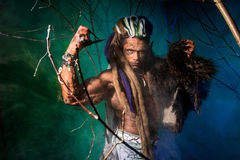 Muscular man with dreadlocks and skin through the trees. Stock Photos