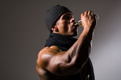 Muscular man drinking alcohol from a bottle stock photo