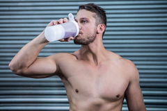 Muscular man drinking protein cocktail Stock Images