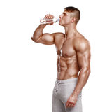 Muscular man drinking water, isolated on white background Royalty Free Stock Images