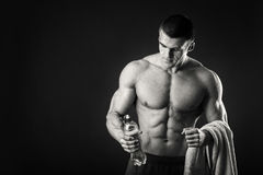 Muscular man drinks water on a dark background Royalty Free Stock Photography