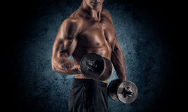 Muscular man with dumbbells on black background Royalty Free Stock Photography