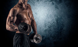 Muscular man with dumbbells on black background. Handsome power athletic man bodybuilder doing exercises with dumbbell. Fitness muscular body on dark background Stock Photos