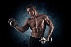 Muscular man with dumbbells on black background Stock Photography