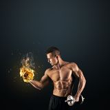 Muscular man with dumbbells on dark background Royalty Free Stock Image