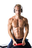 Muscular man with earphones listening to music Stock Image