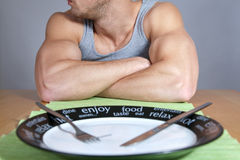 Muscular man with empty plate Royalty Free Stock Image