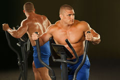 Muscular man  is engaged on the xtrainer machines. Fitness - powerful muscular man  is engaged on the xtrainer machines at the gym Stock Images