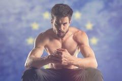 Muscular man with EU flag behind. Muscular man royalty free stock photos
