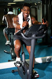 Muscular man on excercise bike at the gym Stock Photo