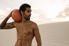 Muscular man with a exercise ball in desert Royalty Free Stock Image