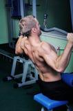 Muscular man exercise in a gym Stock Photos