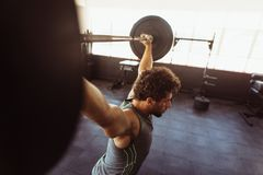 Muscular man exercising with barbell. Fit young man working out with heavy weights at cross training gym Stock Photo
