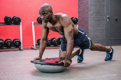 Muscular man exercising with bosu ball Royalty Free Stock Photography