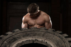 Muscular Man Exercising Crossfit Workout By Tire Flip Stock Images