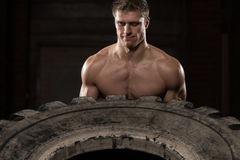 Muscular Man Exercising Crossfit Workout By Tire Flip Stock Photo