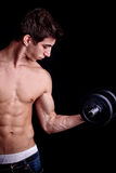 Muscular man exercising with dumbbell Stock Images