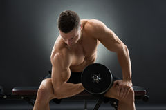 Muscular Man Exercising With Dumbbells On Chair Stock Images