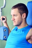 Muscular man exercising in a gym Royalty Free Stock Image