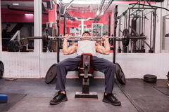 Muscular man exercising in the gym Stock Images