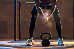 Muscular man exercising with kettlebell in gym. Stock Photos
