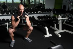 Muscular Man Exercising Quadriceps With Dumbbells. Strong Man In The Gym Exercising Hamstrings With Dumbbells - Muscular Athletic Bodybuilder Fitness Model Royalty Free Stock Images