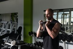 Muscular Man Exercising Quadriceps With Dumbbells. Strong Man In The Gym Exercising Legs With Dumbbells - Muscular Athletic Bodybuilder Fitness Model Exercise Stock Images