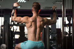 Muscular Man Exercising Shoulders On Machine Stock Images