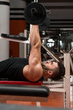 Muscular Man Exercising Triceps With Barbell Stock Photo