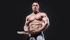 Muscular man fasten lifting belt posing over dark royalty free stock photo