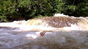 Scary hand sticking out of the river. Muscular man filmed on a sunny day, on the side of a river, with trees in the background stock video footage