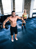Muscular man and fit woman lifting dumbbells Royalty Free Stock Photography