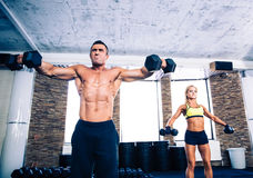 Muscular man and fit woman lifting dumbbells Royalty Free Stock Photos