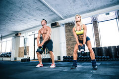 Muscular man and fit woman lifting kettle ball Stock Image