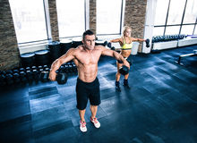 Muscular man and fit woman workout with dumbbells Royalty Free Stock Photos