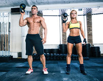 Muscular man and fit woman workout with kettle ball Royalty Free Stock Photo