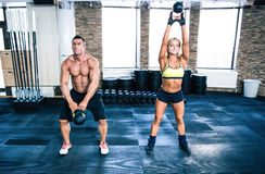 Muscular man and fit woman workout with kettle ball Royalty Free Stock Images
