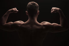 Muscular man flexing arms and shoulders posing topless Royalty Free Stock Photos