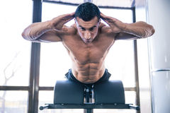 Muscular man flexing back muscles on bench Stock Images
