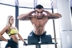 Muscular man flexing back muscles on bench Royalty Free Stock Photography