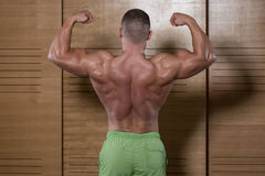 Muscular Man Flexing Back Muscles Pose Stock Photography