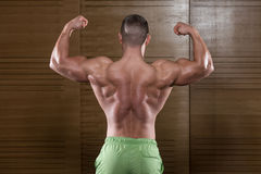 Muscular Man Flexing Back Muscles Pose Stock Photos