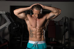 Muscular Man Flexing Muscles In Gym Stock Photo
