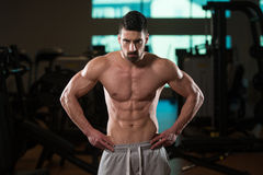 Muscular Man Flexing Muscles In Gym. Young Man Standing Strong In The Gym And Flexing Muscles - Muscular Athletic Bodybuilder Fitness Model Posing After Stock Image