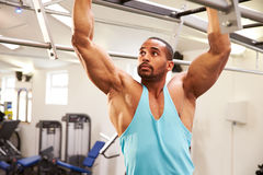 Muscular man flexing muscles on monkey bars at a gym Royalty Free Stock Photography